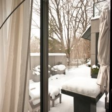 """Winter time Exterior of modern North American house in the city, seen outside bedroom window."""